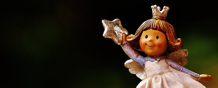girl angel holding star figurine closeup photo