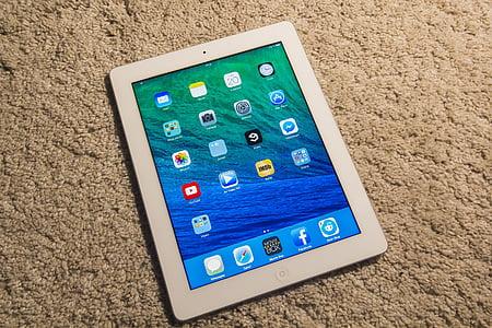 white iPad turned-on on beige textile