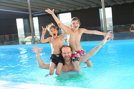man with children swimming in the pool