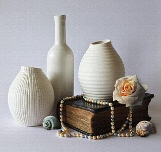 three white ceramic vases and brown book