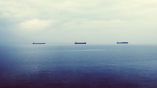 silhouette of ships on body of water