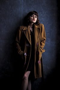 woman wearing brown trench coat stands next to blue painted wall