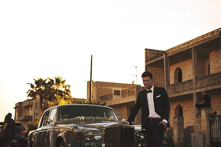 man in black tuxedo standing infront of classic car
