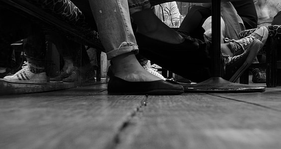 grayscale photo of person foot wearing a slip on shoe