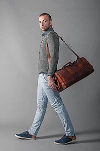 man wearing brown leather duffel bag