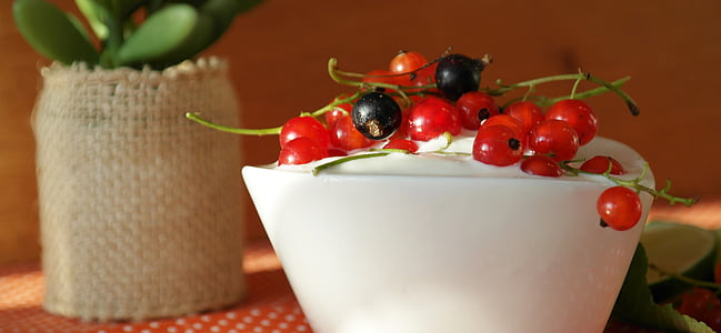red and black currants on top on white cream