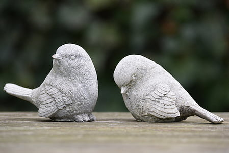 selective focus photography of two grey concrete bird figurines