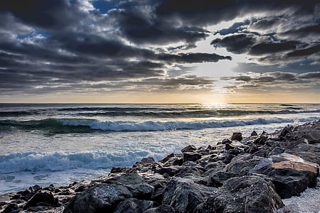landscape photography of coastal rocks under cloudy sky