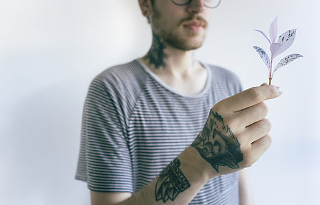 man with tattoos wearing black and white striped shirt holding white leafed plant