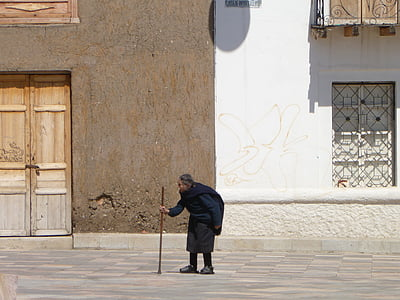 person walking on street while holding walking cane