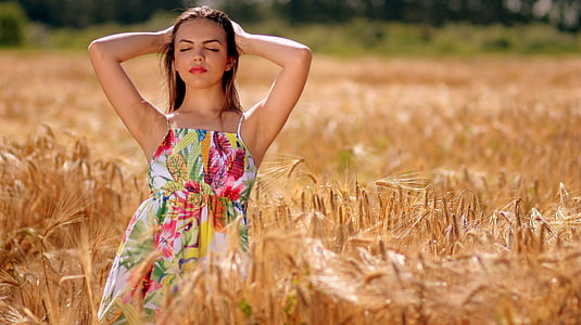selective focus photography of woman in floral spaghetti strap dress in wheat field