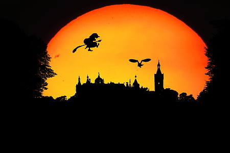 silhouette of witch and castle during sunset