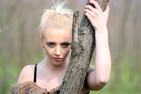 woman standing near brown tree