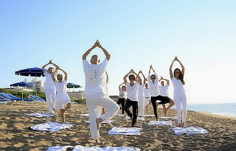 people wearing white shirts exercising on sea shore