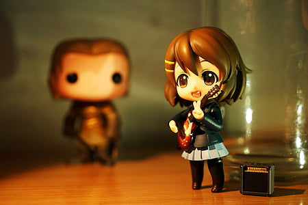 female brunette anime character playing guitar figurine on brown wooden surface