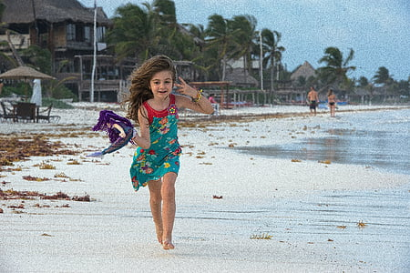 panning photography of girl holding purple textile running on seashore