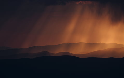 silhouette of mountain under crepuscular clouds