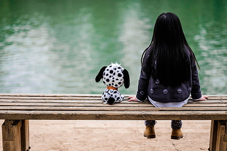 girl in black jacket and blue denim pants sitting beside dalmatian puppy plush toy during daytime