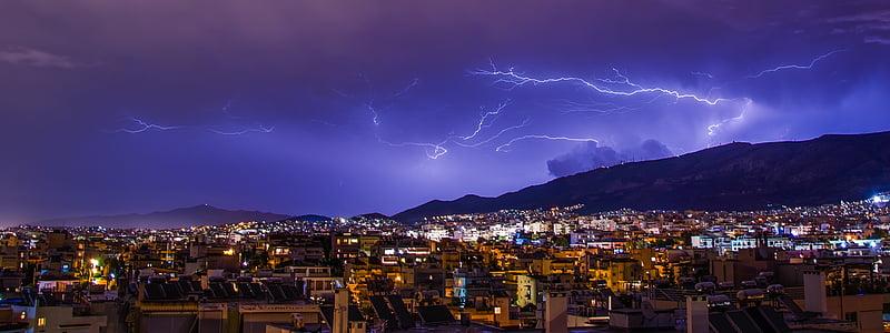 lightning occurring above mountain near city