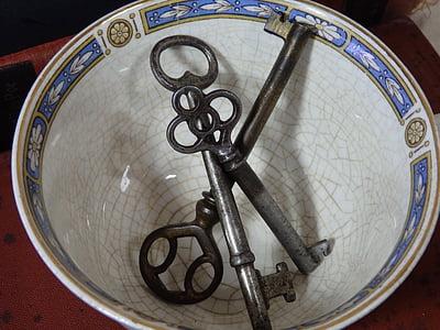 three gray skeleton keys on white bowl