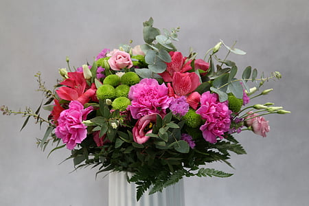pink, red, and green petaled flowers in white vase close up photo