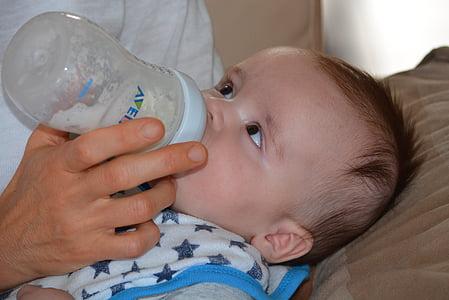 person feeding baby milk in bottle
