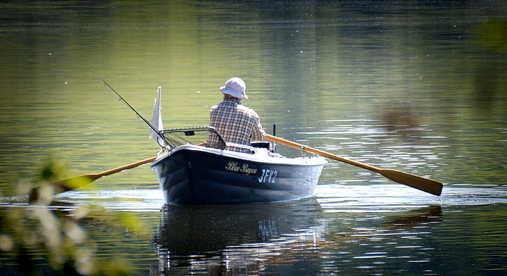man riding black boat using oar