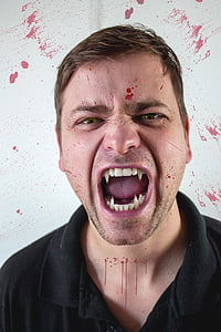 photo of man in black polo shirt with fangs