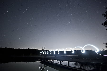 grayscale photo of lake with dock under starry night