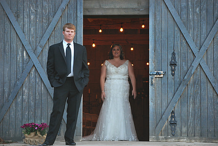 bride and groom standing on barnyard
