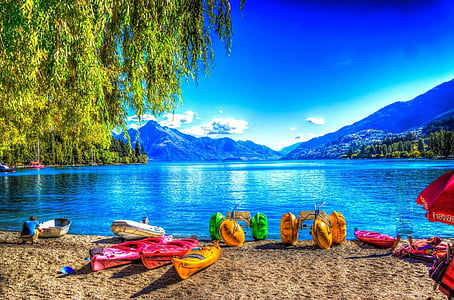 assorted-color kayak and boat near body of water background of mountains