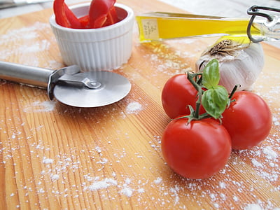 tomatoes beside garlic and pizza slicer