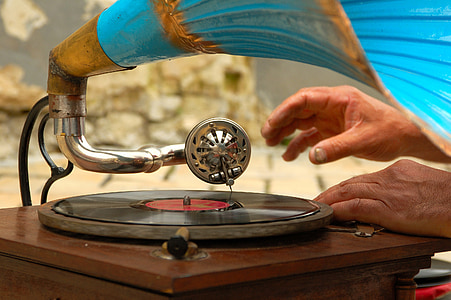 person touching gramophone