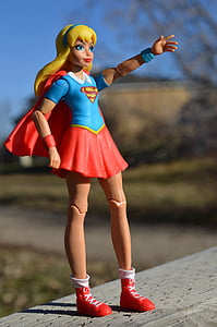 macro photograph of DC Super Hero Girls Supergirl action figure on gray wooden surface