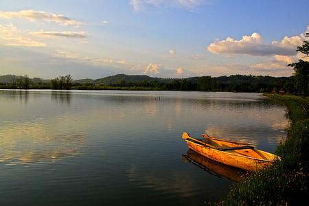 orange row boat over body of water