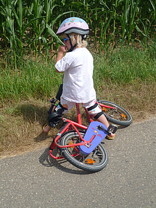 boy riding red bicycle on road