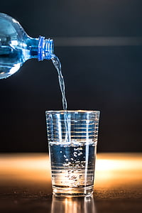 time lapse photo of water from bottle down to clear drinking glass