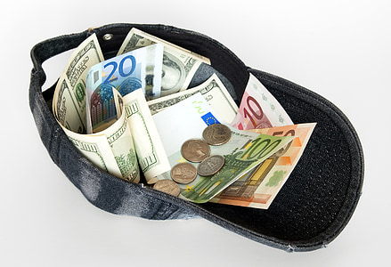 assorted banknotes and coins in black cap