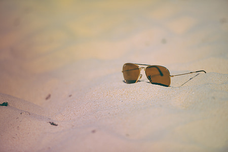 photo of brown tinted sunglasses on gray sand