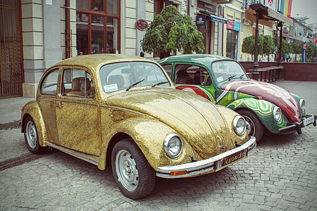 two assorted-color Volkswagen Beetle coupe