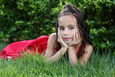 girl in red dress on green grass