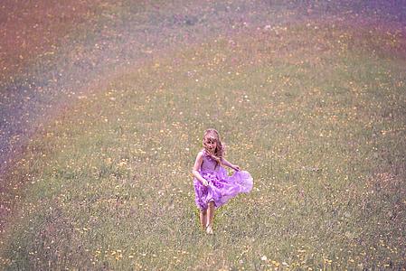 girl wearing purple dress running on grass field