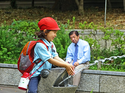 girl in school uniform washing her hands near sitting man
