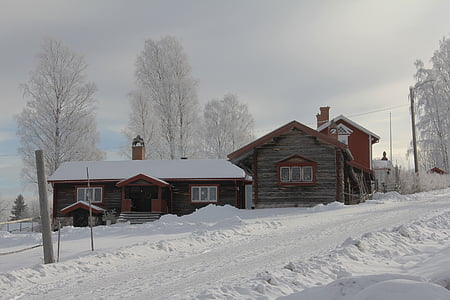 brown wooden house surrounded by snow