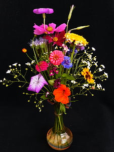 red-blue-and-yellow petaled flowers in amber glass vase