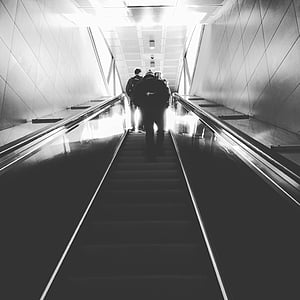 grayscale photo of people climbing using escalator stairs