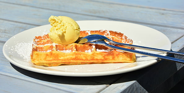 waffle with ice cream on top in white ceramic plate
