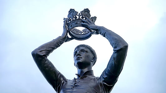 male statue holding crown under white clouds