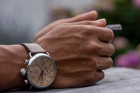 person wearing silver-colored chronograph watch leaning on gray surface