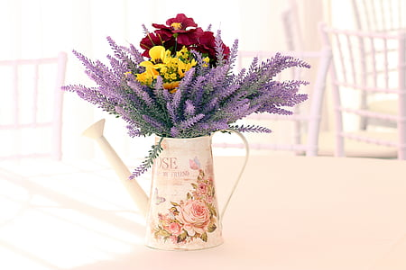 red and yellow petaled flower arrangement with white floral ceramic watering can table decor